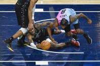 Minnesota Timberwolves forward Jarred Vanderbilt, left, and Miami Heat forward Trevor Ariza vie for a loose ball during the first half of an NBA basketball game Friday, April 16, 2021, in Minneapolis. (AP Photo/Craig Lassig)