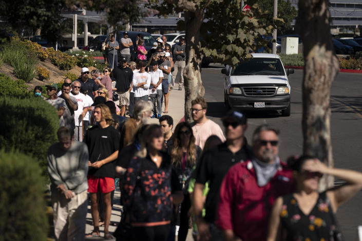 People wait in line to vote outside a vote center Tuesday, Sept. 14, 2021, in Huntington Beach, Calif. With Gov. Gavin Newsom's fate at stake, Californians on Tuesday cast the last of the ballots that will decide whether he continues to lead them or if the nation's most populous state veers in a more conservative direction amid anger over his actions during the COVID-19 pandemic. (AP Photo/Jae C. Hong)