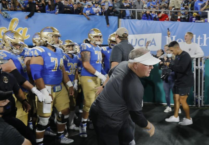 PASADENA, CA - SEPTEMBER 18, 2021: UCLA coach Chip Kelly dashes on to the field ahead.