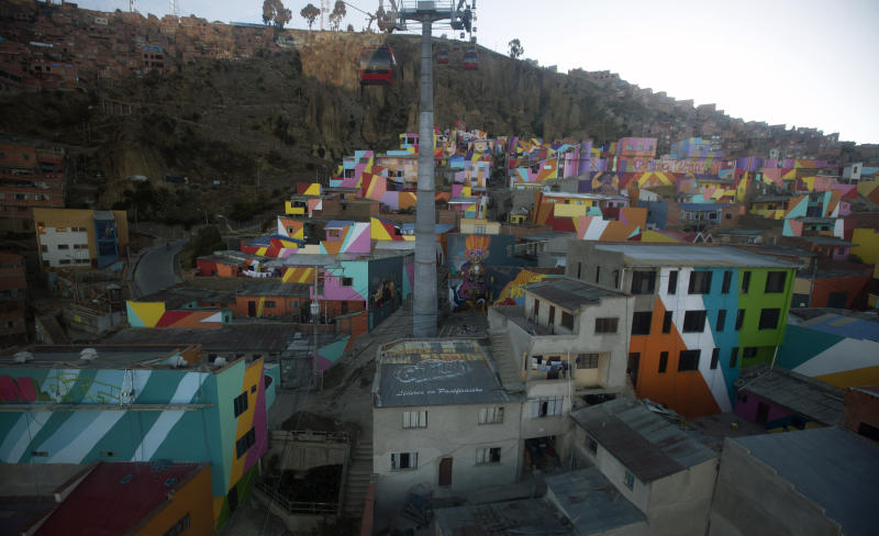 This May 31, 2019 photo shows a view from a cable car of the Chualluma neighborhood, in La Paz, Bolivia. Images of indigenous Aymara women selling produce and spices in the streets, hummingbirds taking flight and multicolored geometrical shapes burst from what once were plain adobe and brick walls on this hillside of Bolivia's capital. (AP Photo/Juan Karita)