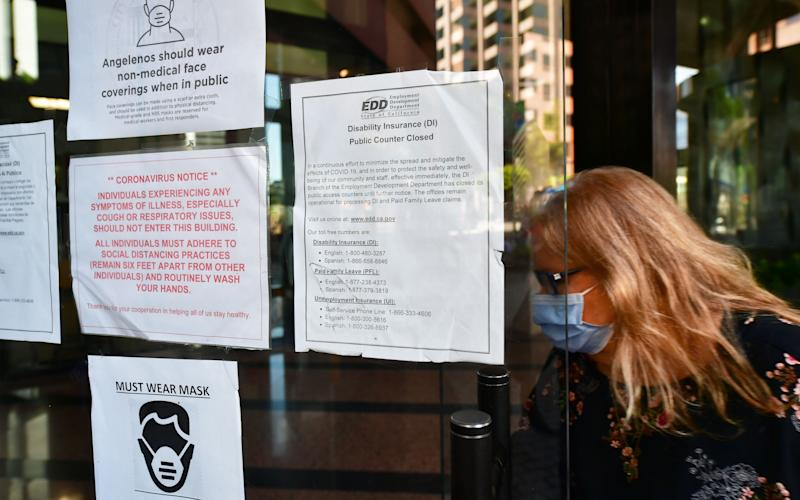 A woman wearing a facemask enters a building where the Employment Development Department has its offices in Los Angeles, California on May 4, 2020, past a posted sign mentioning the closure of the offices's public access counters due to the coronavirus pandemic. - Dismal US employment figures are expected with the release Friday May 8 of figures for April's US jobs report, with 30 million Americans filing for unemployment in the last six weeks. (Photo by Frederic J. BROWN / AFP) (Photo by FREDERIC J. BROWN/AFP via Getty Images)