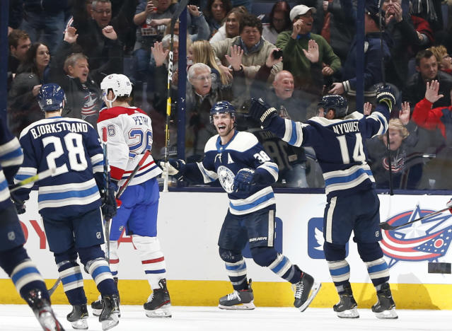 Columbus Blue Jackets' Boone Jenner, center, celebrates his goal against the Montreal Canadiens during the third period of an NHL hockey game Tuesday, Nov. 19, 2019, in Columbus, Ohio. The Blue Jackets beat the Canadiens 5-2. (AP Photo/Jay LaPrete)