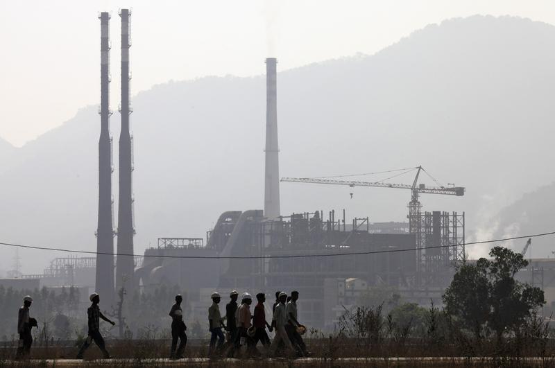 Workers walk in front of the Vedanta Aluminium factory in Lanjigarh