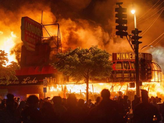 Protesters gather in front of a liquor store in flames near the police building in Minneapolis (AFP via Getty Images)