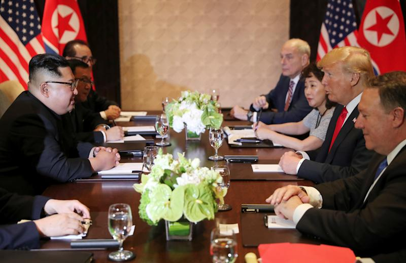 President Donald Trump, with Yun Hyang Lee at his side, speaks to North Korea's leader Kim Jong Un before their expanded bilateral meeting at the Capella Hotel on Sentosa island in Singapore June 12, 2018.