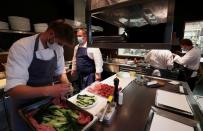FILE PHOTO: Employees at the 2 stars Michelin restaurant Le Chalet de la Foret serve customers in Brussels