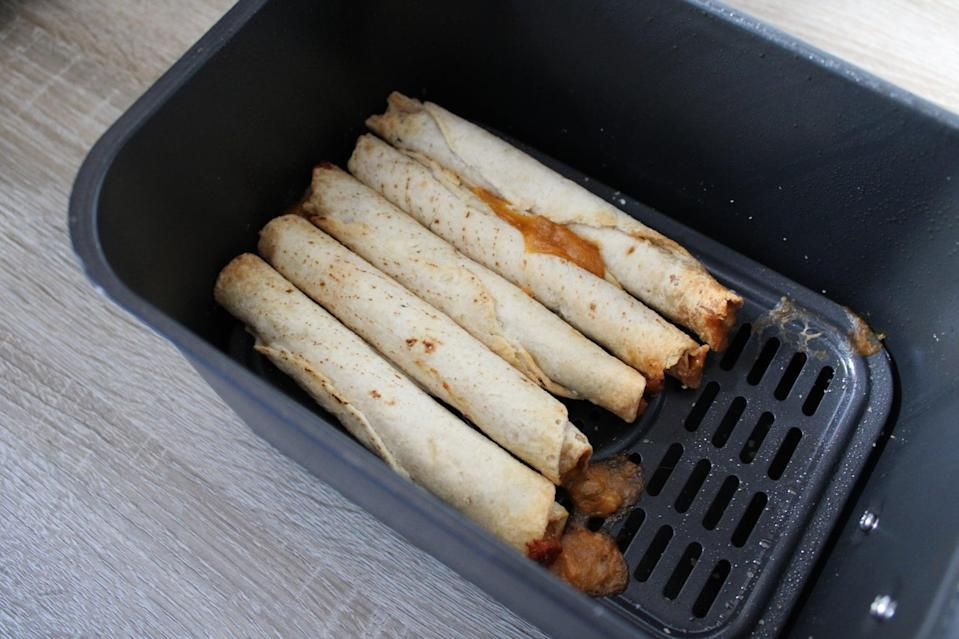 <p>After eight minutes, your taquitos should be hot, and you might see some cheese or filling start to poke out. When this happens, you know they're done! If you like yours extra crispy, you can leave them in for another minute or two. Remove them from the air fryer.</p>
