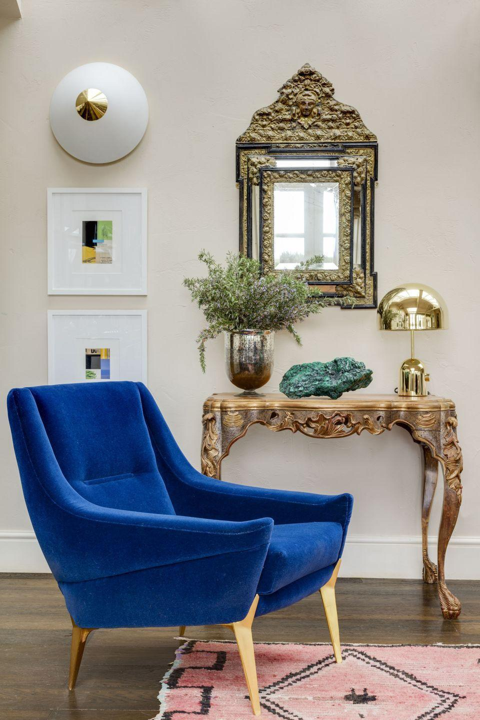 """<p>""""I walked by this chair on the Pimlico road and fell in love with the electric blue mohair. It's one of a pair from the 1950s by Charles Ramos, and they're both supremely comfortable. The lamp is by Tom Dixon, I am a huge fan. The collages on the wall are by American artist Cecil Touchon and I love how they look hung under this strange conical 60s wall light.""""</p>"""