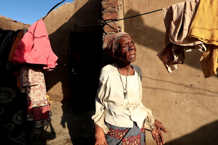 "Tchacaca Quembo stands outside her damaged house in the aftermath of Cyclone Idai, in the village of Cheia, which means ""Flood"" in Portuguese, near Beira, Mozambique April 1, 2019. Photo: Zohra Bensemra/Reuters)"