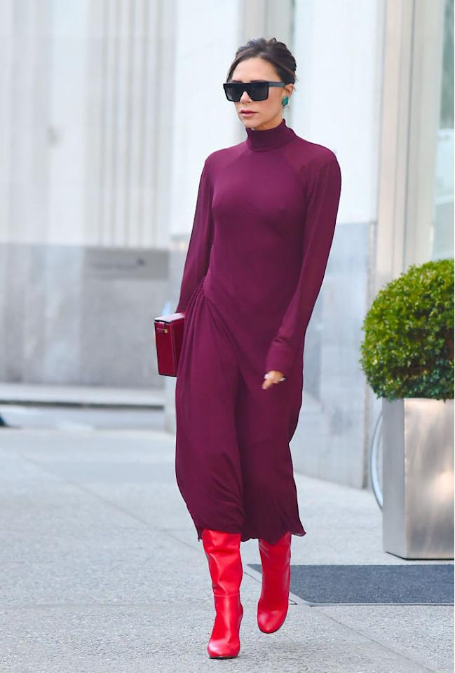 <p>The designer proved she's the Queen of colour blocking in a plum-hued rollneck dress and clashing red boots. Finished of course, with a pair of Beckham-approved sunnies.<em> [Photo: Getty]</em> </p>