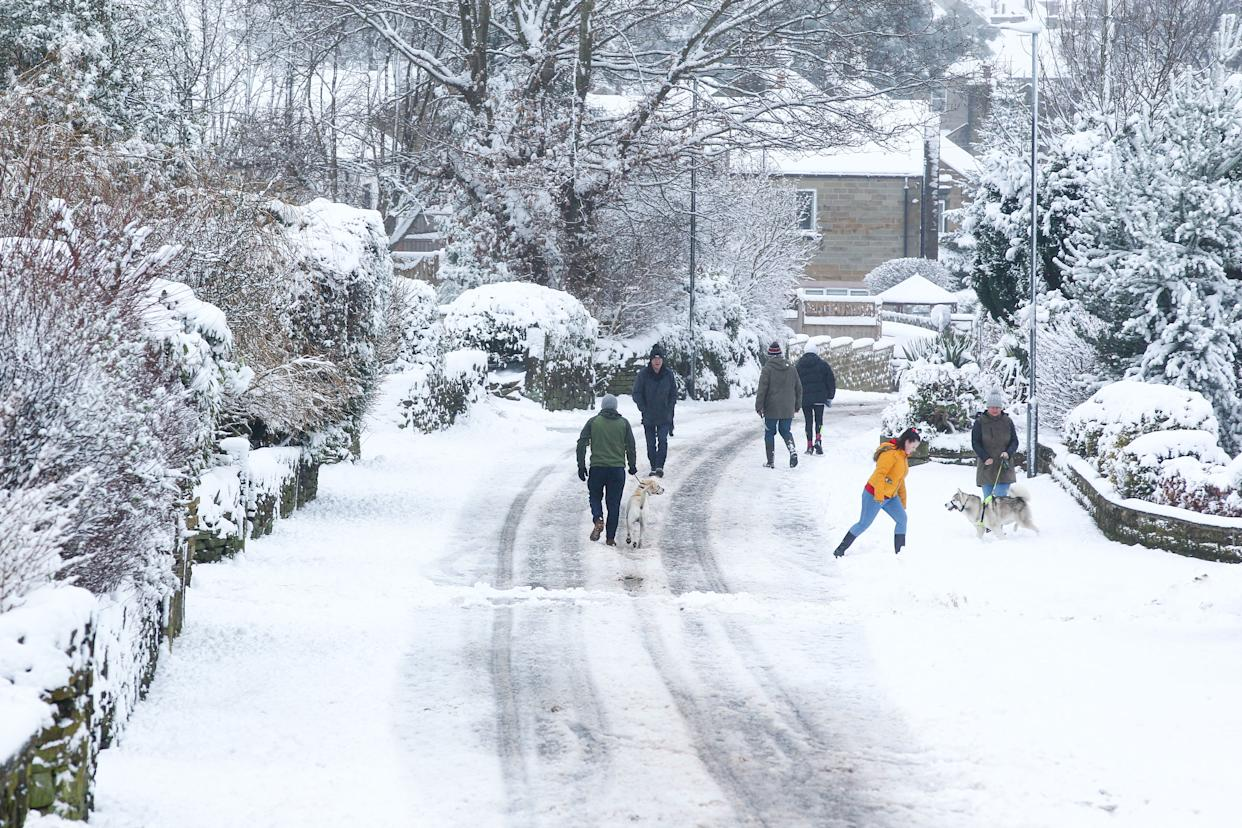 People walk along a snow-covered lane in West Yorkshire. Heavy snow fell overnight in West Yorkshire, causing dangerous driving conditions. (Photo by Adam Vaughan / SOPA Images/Sipa USA)