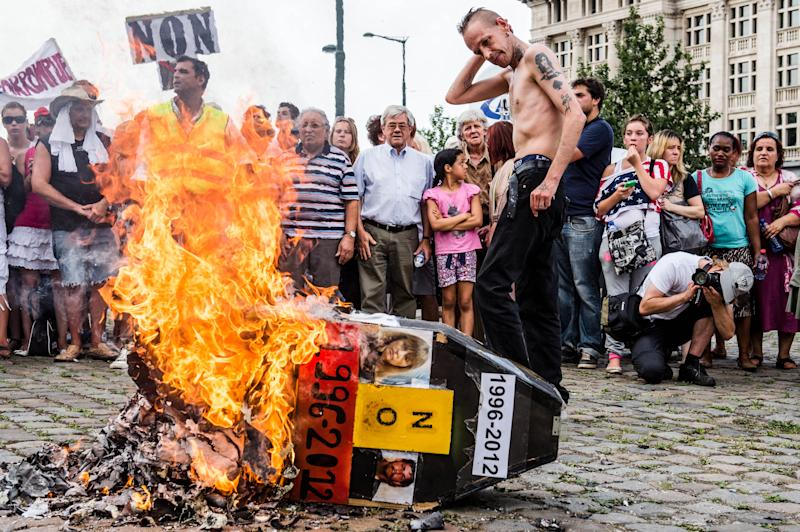 FILE- In this Aug. 19, 2012 file photo, demonstrators gather around a burning mock coffin with the pictures of Belgium's child killer Marc Dutroux and his ex-wife Michelle Martin during a march to remember their victims, in Brussels. Martin, who is scheduled to be released on Tuesday, Aug. 28, 2012, was convicted to 30 years in prison for helping her husband kidnap, rape and kill several young girls in the 1990's. She has served 16 years of her term but could be released within days. (AP Photo/Geert Vanden Wijngaert, File)