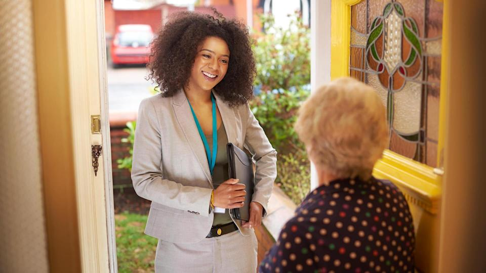 A young smartly dressed woman is standing at the front door smiling at a senior woman who has opened it .