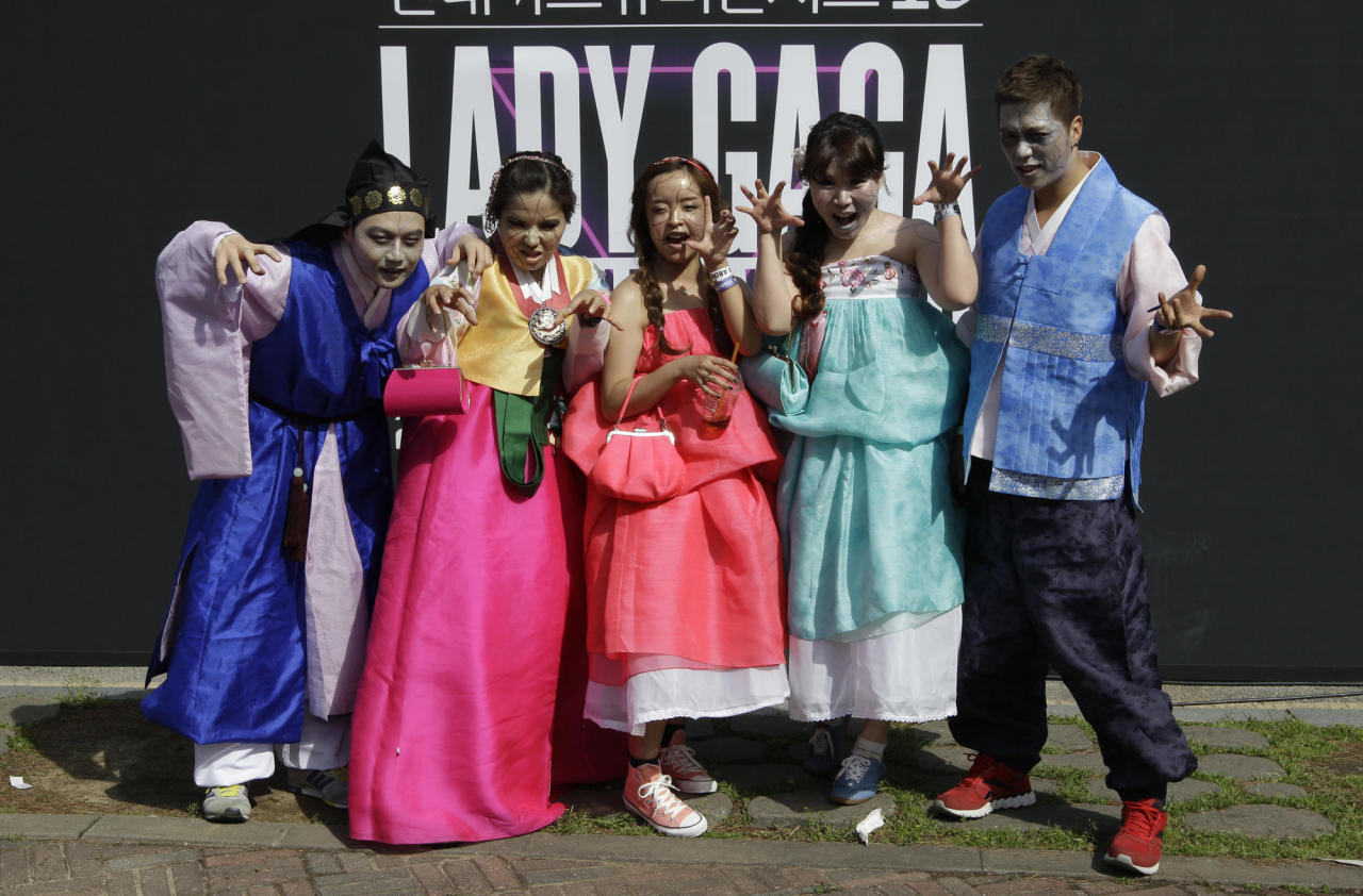 US pop diva Lady Gaga's fans wearing South Korean traditional dresses pose for the media as they wait for her concert in front of the venue in Seoul, South Korea, Friday, April 27, 2012. (AP Photo/Lee Jin-man)