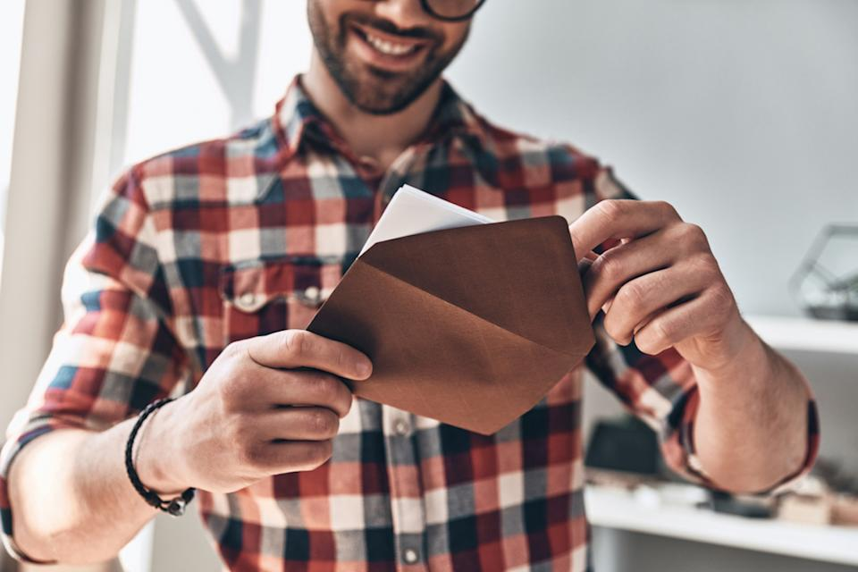 closeup of man putting greeting card in envelope and smiling