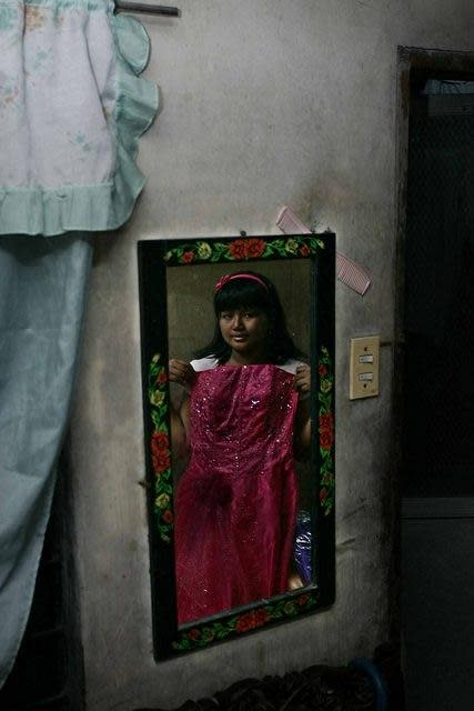 Fifteen year old Marielle Mae Estoy, a cancer warrior, shows a dress she wore to her school prom in Pasig City, east of Manila, on 19 March 2012. Estoy has been fighting leukemia since she was 5. (Mike Alquinto/NPPA Images)