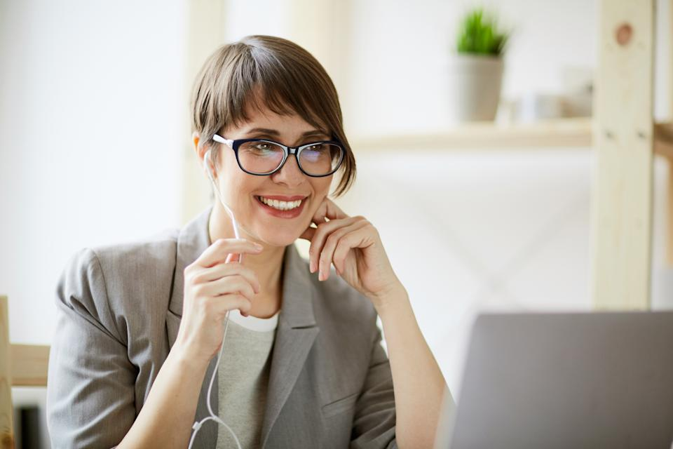 Portrait of young successful businesswoman wearing creative haircut and glasses smiling cheerfully while holding videochat using hands free mic and laptop at workplace in modern office against window