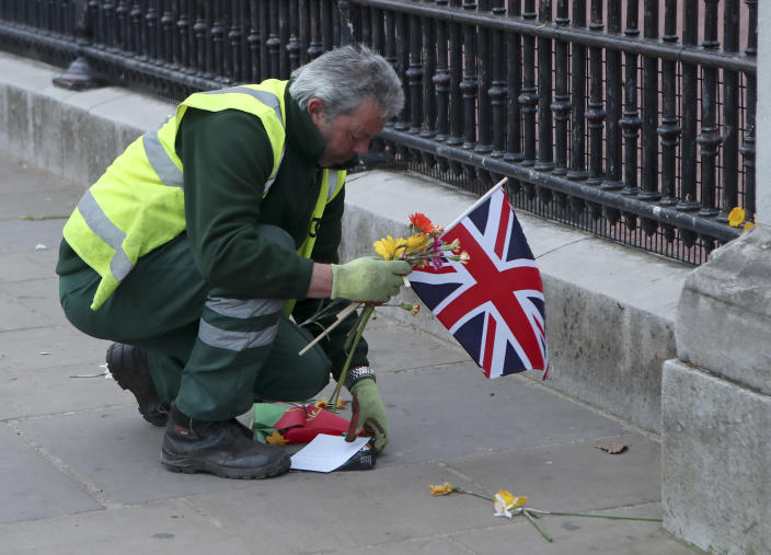 A worker clears away tributes left in honor of Britain's Prince Philip from outside Buckingham Palace in London on Saturday, April 10, 2021. Prince Philip, the irascible and tough-minded husband of Queen Elizabeth II who spent more than seven decades supporting his wife in a role that both defined and constricted his life, has died, Buckingham Palace said Friday. He was 99. (AP Photo/Tony Hicks)