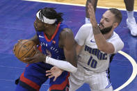 Detroit Pistons forward Jerami Grant (9) spins to the basket while defended by Orlando Magic guard Evan Fournier (10) during the second half of an NBA basketball game, Tuesday, Feb. 23, 2021, in Orlando, Fla. (AP Photo/Phelan M. Ebenhack)