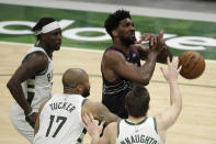 Philadelphia 76ers' Joel Embiid is fouled by Milwaukee Bucks' P.J. Tucker (17) during the second half of an NBA basketball game Thursday, April 22, 2021, in Milwaukee. (AP Photo/Aaron Gash)