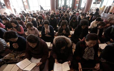 Parents pray for their children's success in the Scholastic Aptitude Test at the Jogye Temple in Seoul, South Korea - Credit:  AP