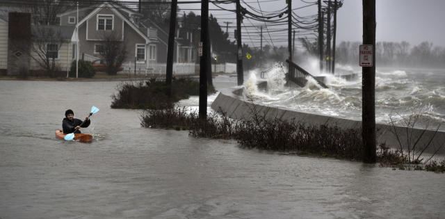 <p>Daniel Cunningham 22, of Quincy dodges waves in his kayak on a flooded E. Squantum Street in the Squantum section of Quincy, Mass., during a nor'easter storm on March 2, 2018. (Photo: Stan Grossfeld/The Boston Globe via Getty Images) </p>