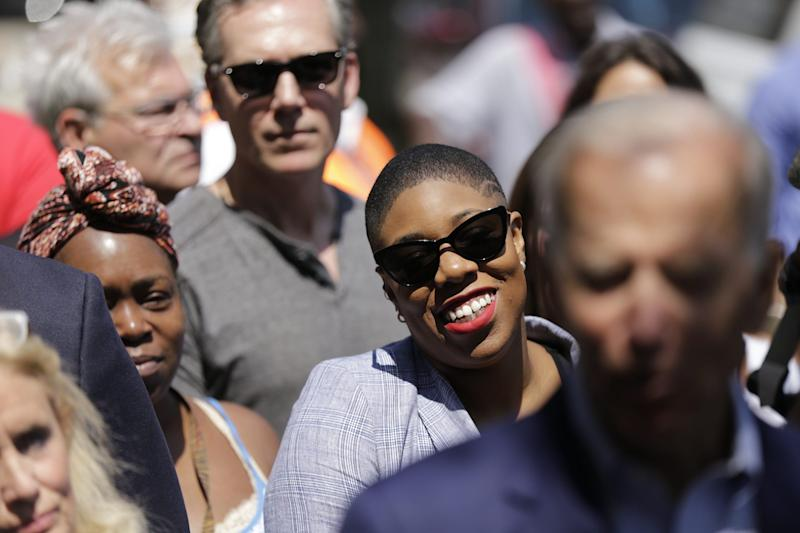 Symone Sanders, senior advisor to 2020 Democratic Presidential Candidate Joe Biden, listens to him speak to the press outside of Detroit One Coney Island in Detroit where he made a campaign stop on Thursday, Aug. 1, 2019.