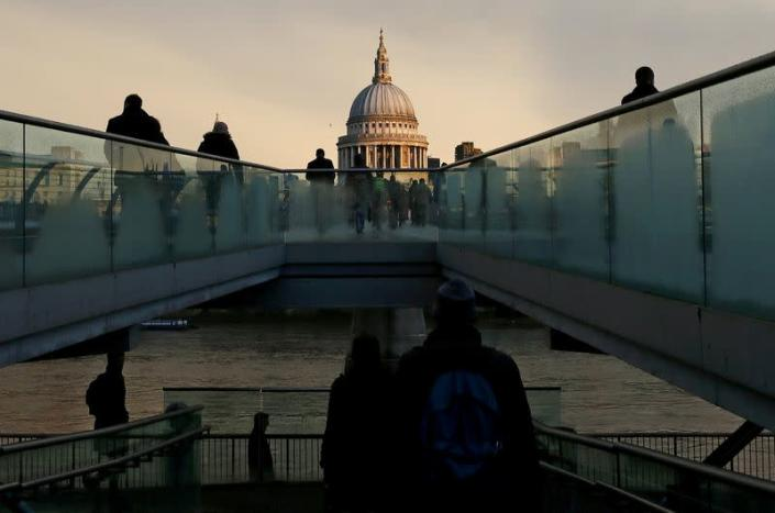 FILE PHOTO: File photo of city workers walking towards St Paul's Cathedral as they cross the Millennium footbridge during sunrise in central London