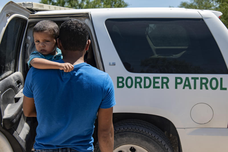 Illegal immigrants prepare to load into a Border Patrol car