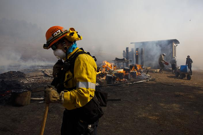 Firefighters and workers try to extinguish smoldering embers on a ranch during the Easy Fire in Simi Valley, Calif. on Oct. 30, 2019. (Photo: Patrick T. Fallon/Bloomberg via Getty Images)