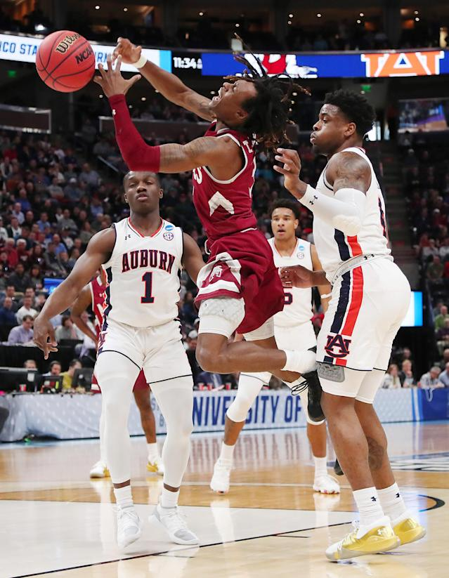 <p>Terrell Brown #3 of the New Mexico State Aggies battles for the ball against Jared Harper #1 and Malik Dunbar #4 of the Auburn Tigers during the first half in the first round of the 2019 NCAA Men's Basketball Tournament at Vivint Smart Home Arena on March 21, 2019 in Salt Lake City, Utah. (Photo by Tom Pennington/Getty Images) </p>