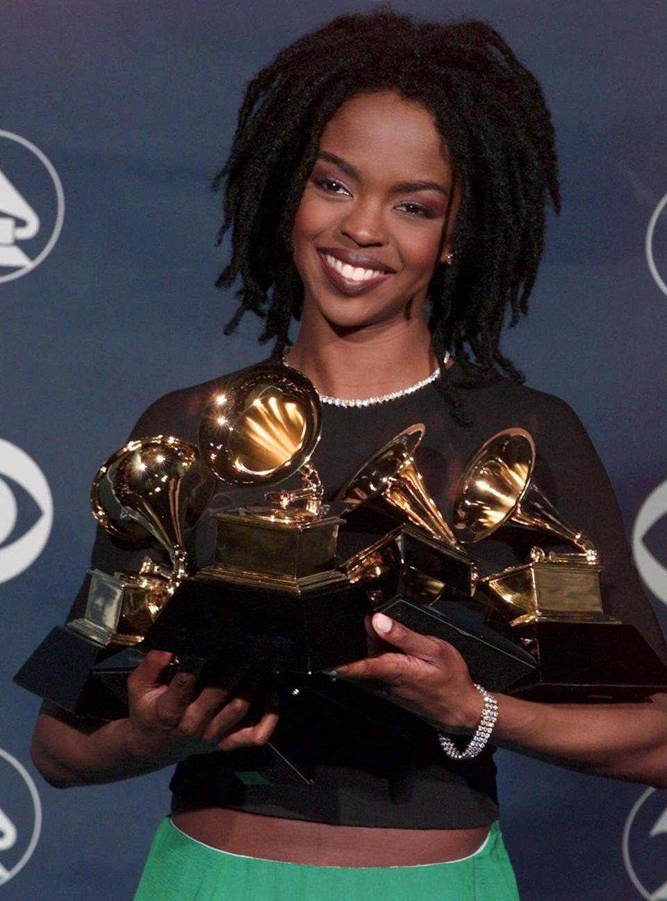 """Lauryn Hill holds her five Grammy Awards during the 41st Annual Grammy Awards at the Shrine Auditorium in Los Angeles on Feb. 24, 1999. Hill's solo debut, """"The Miseducation of Lauryn Hill,"""" was the first rap-related album nominated for album of the year, which it won in 1999. She also won best new artist that year, and is one of two rap acts to do so."""