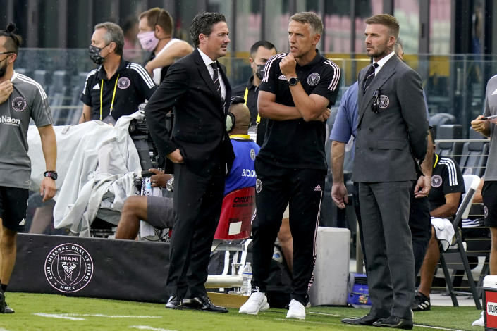 David Beckham, right, owner and president of soccer operations for Inter Miami, talks with coach Phil Neville, center, and David Gardner, left, before an MLS soccer match between Inter Miami and CF Montreal, Wednesday, May 12, 2021, in Fort Lauderdale, Fla. (AP Photo/Lynne Sladky)