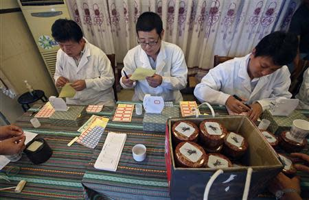 Judges prepare labels before they measure the weights of crickets during the Beijing Cricket Fighting Competition September 19, 2013. REUTERS/Kim Kyung-Hoon