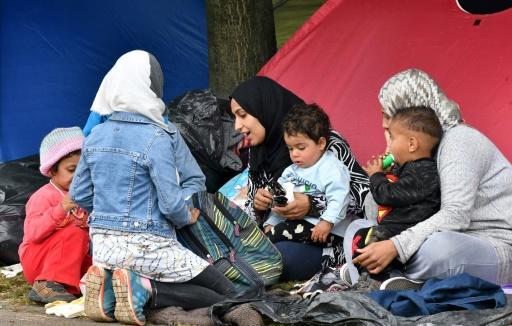 Migrant women with children sit outside their tent, in the park accross from the national ibrary in Sarajevo, on May 14, 2018
