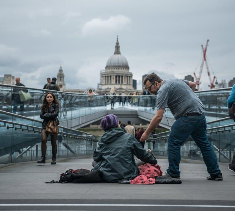 A man in a grey t-shirt gives money to a homeless person sitting on a bridge in central London