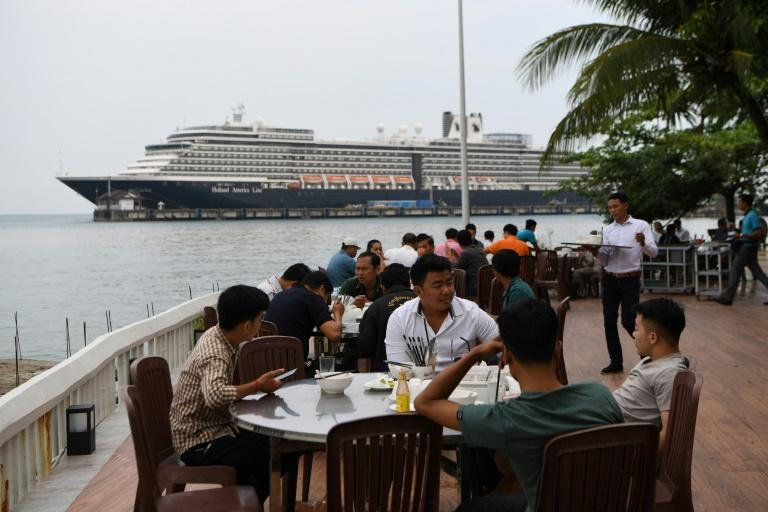 Diners have lunch in the foreground of the Westerdam cruise ship in Sihanoukville