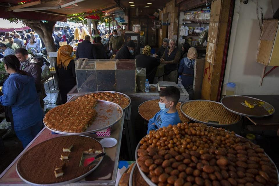 Large round trays filled with desserts cover tables at a crowded market.