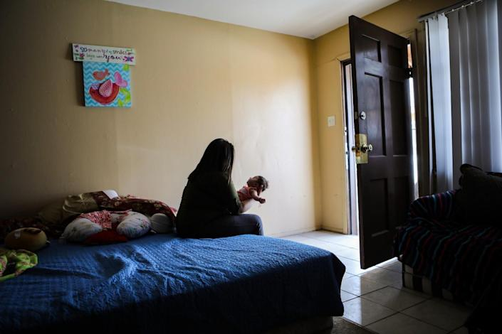 Luz holds her infant daughter while living in Las Cruces, N.M.