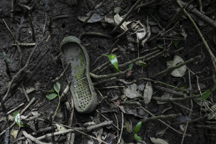 The sole of a shoe lays near a clandestine grave site in Puquita, a tropical mangrove island near Alvarado in the Gulf coast state of Veracruz, Mexico, Thursday, Feb. 18, 2021. Investigators from the National Search Commission found three pits with human remains and plastic bags inside. The number of bodies there has not yet been determined. (AP Photo/Felix Marquez)