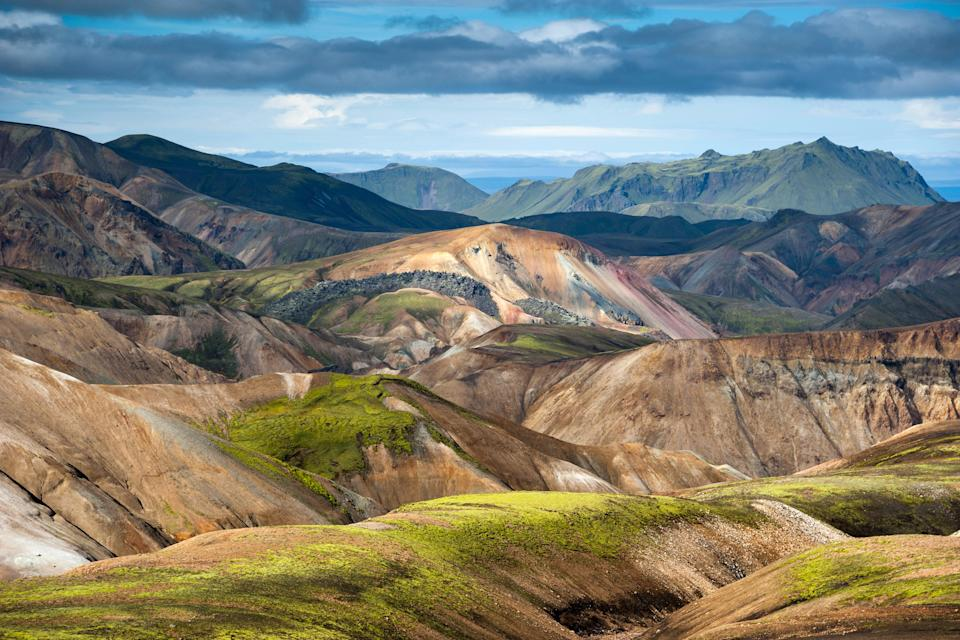 """Located in Iceland's southern Highlands, the area of Landmannalaugar has some of the most <a href=""""https://www.cntraveler.com/gallery/most-colorful-places-in-the-world?mbid=synd_yahoo_rss"""" rel=""""nofollow noopener"""" target=""""_blank"""" data-ylk=""""slk:colorful landscapes"""" class=""""link rapid-noclick-resp"""">colorful landscapes</a> in the country thanks to its high geothermal activity. It's an extremely popular hiking area during the summer months, where lucky visitors can be surrounded by a veritable kaleidoscope of greens, oranges, reds, blacks, browns, and more."""
