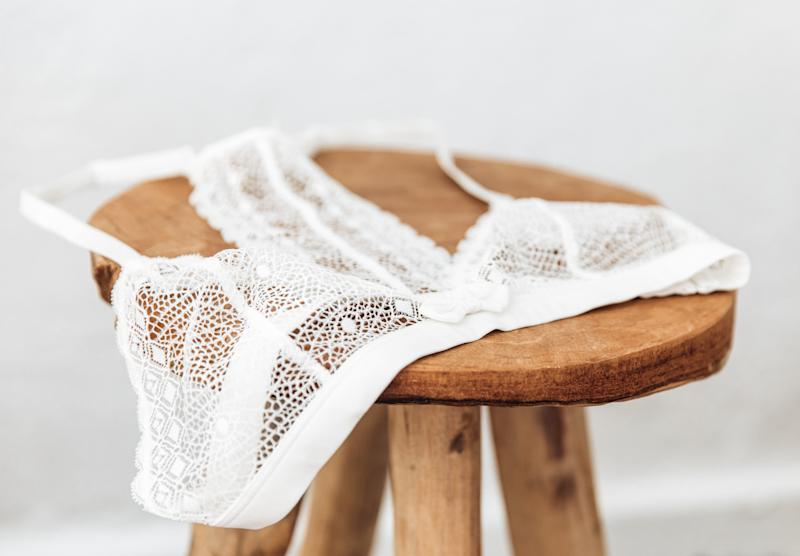White delicate lace bra on a wood stool