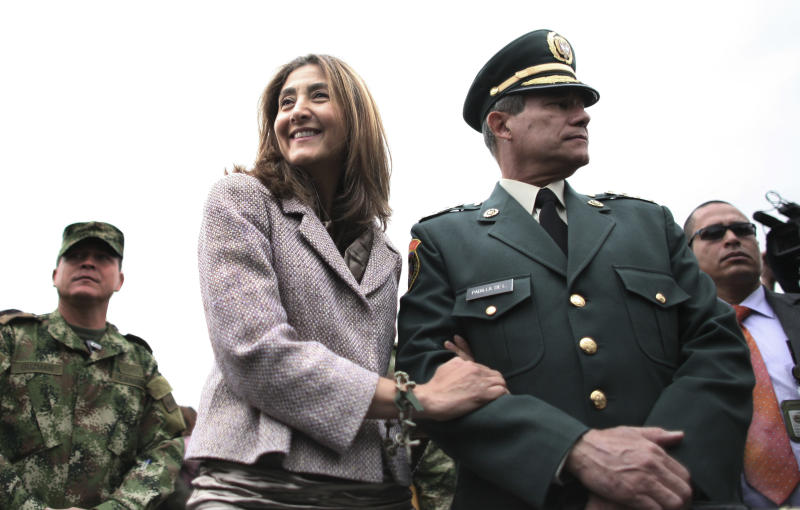 FILE - In this July 2, 2010 file photo, former Colombian rebel hostage Ingrid Betancourt, right, smiles as she stands with the Commander of Colombia's Armed Forces, Gen. Freddy Padilla, during a ceremony in Bogota, Colombia, marking the second anniversary of Operation Jaque, in which Betancourt along with over a dozen hostages were rescued. A spokesman for Colombia's Green Party says Betancourt will seek to represent it in next year's presidential elections. (AP Photo/William Fernando Martinez, File)