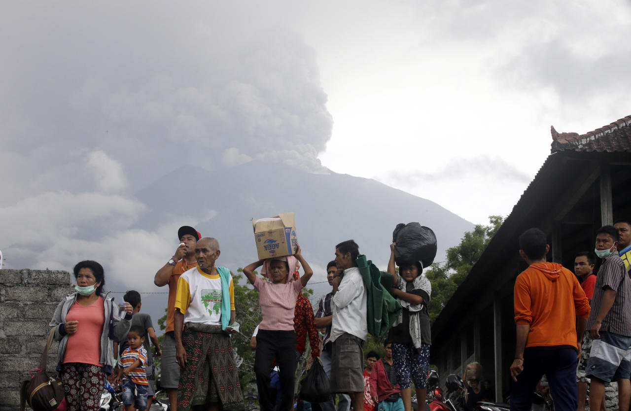 <p>Villagers carry their belongings during an evacuation following the eruption of Mount Agung in Karangasem. The volcano on the Indonesian island of Bali has rumbled into life with a series of eruptions that temporarily disrupted some international flights to the popular tourist destination and dusted nearby resorts and villages with a thin layer of ash. (AP Photo/Firdia Lisnawati </p>