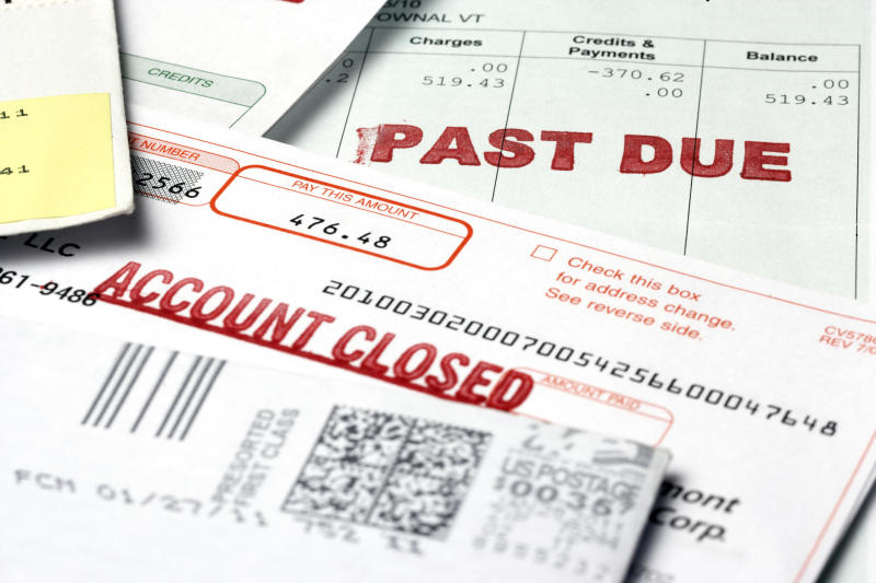 "Stack of bills labeled ""past due"" and ""account closed."""