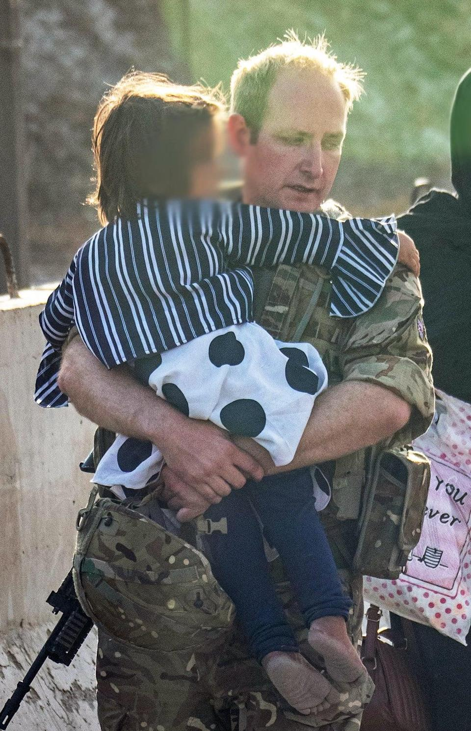 A member of the UK Armed Forces carrying a child at Kabul airport. (LPhot Ben Shread/MoD) (PA Media)