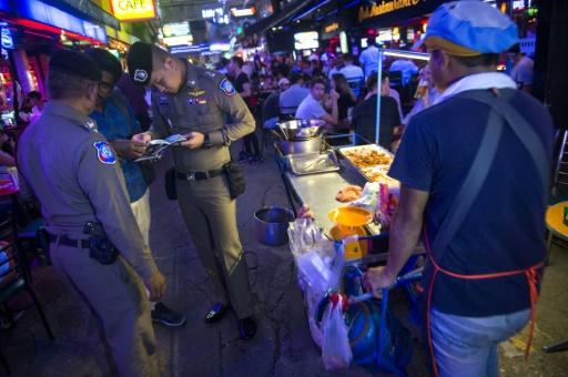 "Police inspect passports in Bangkok's Patpong district during an ""X-Ray Outlaw Foreigner"" operation"