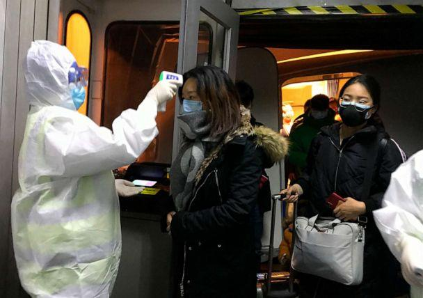 PHOTO: Health Officials in hazmat suits check body temperatures of passengers arriving from the city of Wuhan, Jan. 22, 2020, at the airport in Beijing, China. (Emily Wang/AP, FILE)