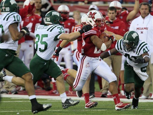 Miami (Ohio) running back Spencer Treadwell (22) is pursued by Ohio defenders Nathan Carpenter (35) and cornerback Ian Wells (41) during a 30-yard run that set up a Miami (Ohio) field goal in the fourth quarter of an NCAA college football game, Saturday, Oct. 27, 2012, in Oxford, Ohio. Miami (Ohio) upset Ohio 23-10. (AP Photo/Al Behrman)
