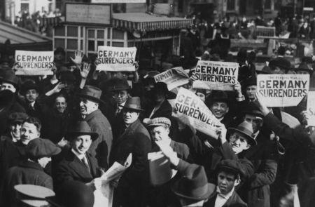 FILE PHOTO: A crowd in Times Square hold up copies of newspapers with a headline about the signing of the Armistice to end World War One, in New York, U.S., November 11, 1918.    U.S. National Archives/via REUTERS